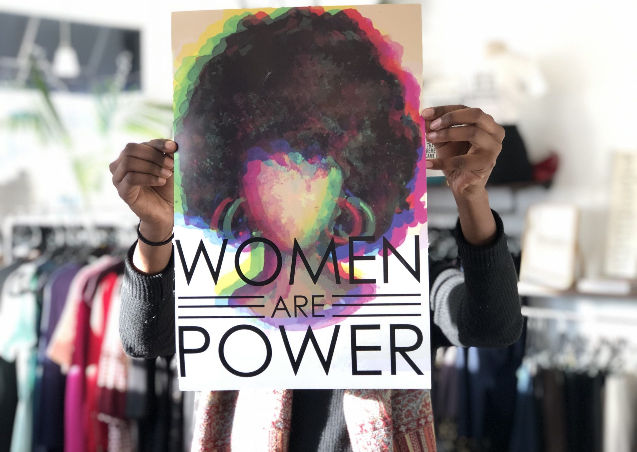"""Women are Power"" sign held up at Sisterhood Boutique"