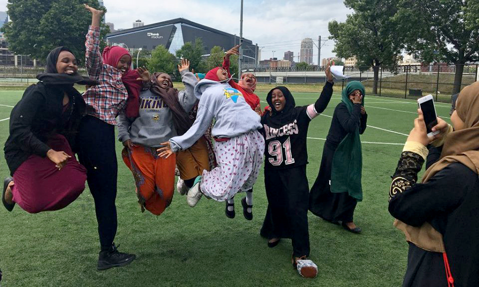 Coyle Center youth program participants jumping for joy in front of US Bank Stadium