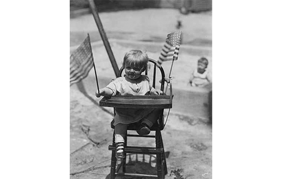 Pillsbury House girl in high chair with flags