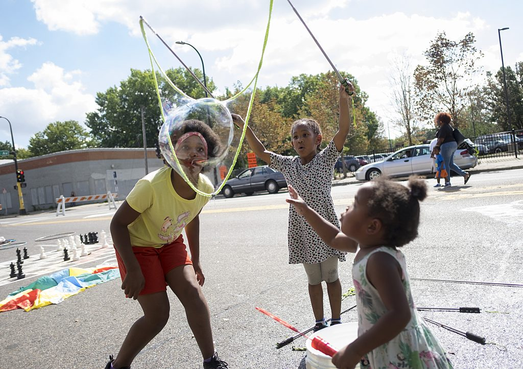 Young girls playing on Broadway Ave during Open Streets