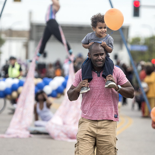 Man holding child on shoulders at Open Streets Broadway Ave